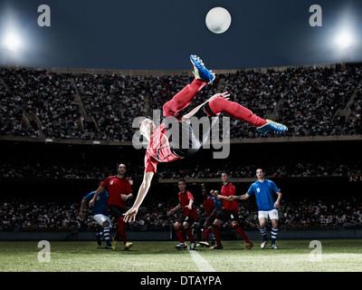 Soccer player kicking ball on field - Stock Photo