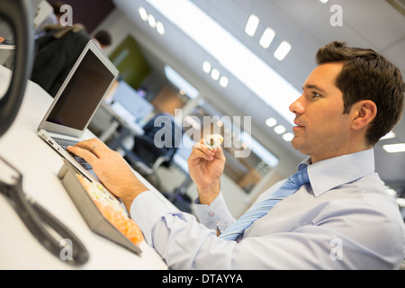 Businessman with laptop eating sushi on his desk - Stock Photo