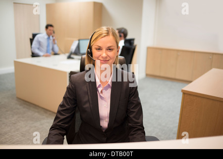 Portrait of smiling woman receptionist in lobby - Stock Photo