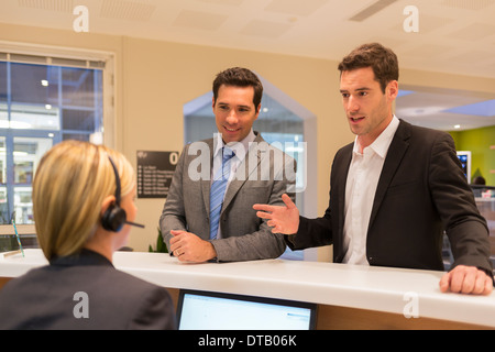 Businessmen communicating with woman receptionist in lobby - Stock Photo