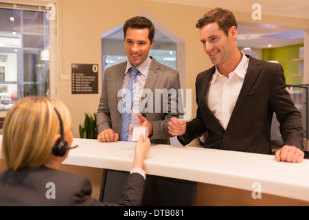 Businessmen communicating with woman receptionist in lobby, she gives a badge - Stock Photo