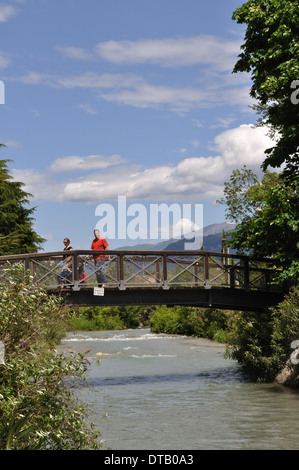 Footbridge over a river flowing into Lake Garda at Riva del Garda, Italy - Stock Photo
