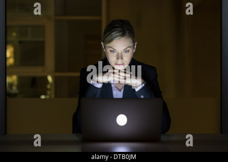 Businesswoman working late in his office on laptop - Stock Photo