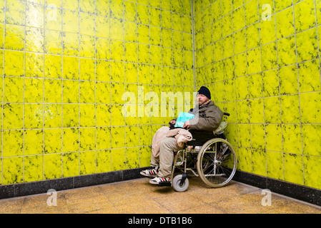 A homeless wheelchair user sits in 'his' corner, where he is living in an underground station. - Stock Photo