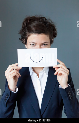 Portrait of mid adult woman holding paper with curve sign, close-up - Stock Photo