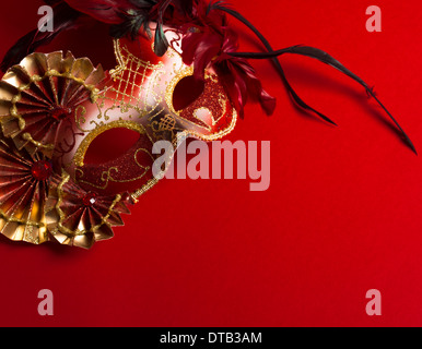 A red and gold venetian, mardi gras mask on a red background - Stock Photo