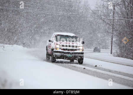 SUV on a highway during a winter storm - Stock Photo