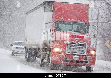 Truck on a highway during a winter storm - Stock Photo