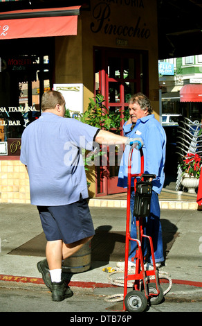 delivery man talks with restaurant owner on sidewalk in North Beach San Francisco - Stock Photo