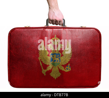 Tourist hand holding vintage leather travel bag with flag of Montenegro - Stock Photo