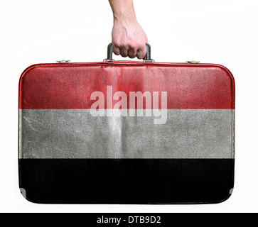 Tourist hand holding vintage leather travel bag with flag of Yemen - Stock Photo
