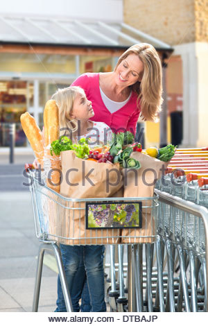 Mother Pushing Daughter In Trolley Outside Supermarket - Stock Photo