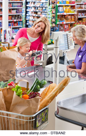 Mother And Daughter Paying For Shopping At Supermarket Checkout - Stock Photo