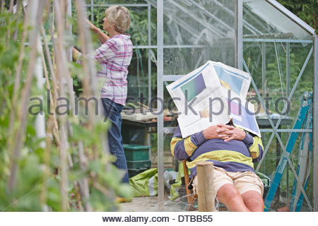 Senior Man Asleep In Vegetable Garden Whilst Wife Works - Stock Photo