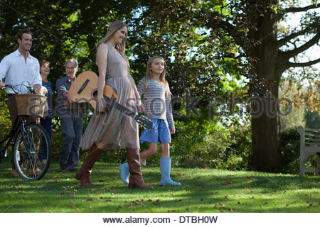Multi-generation family with bicycle, apples and guitar in orchard - Stock Photo