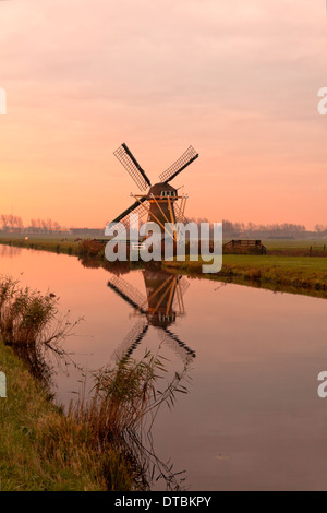 Drainage mill ''Hope springs eternal'' during a colorful sunrise in Voorhout, South Holland, The Netherlands. - Stock Photo