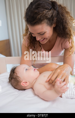 Mother looking at baby lying in crib - Stock Photo