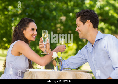 Couple with champagne flutes sitting at outdoor café - Stock Photo