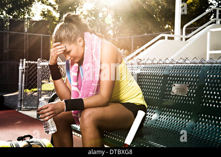 Female tennis player on bench with head in hands - Stock Photo