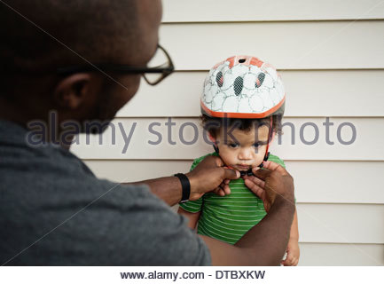 Father putting on helmet for son - Stock Photo