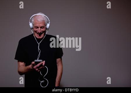 Portrait of senior man wearing headphones and using MP3 player - Stock Photo