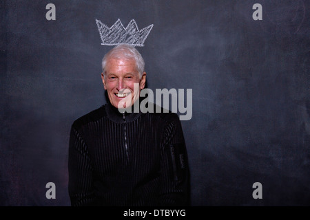 Portrait of senior man in front of chalked crown on blackboard - Stock Photo