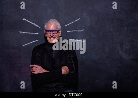 Portrait of senior man in front of chalked lines on blackboard - Stock Photo
