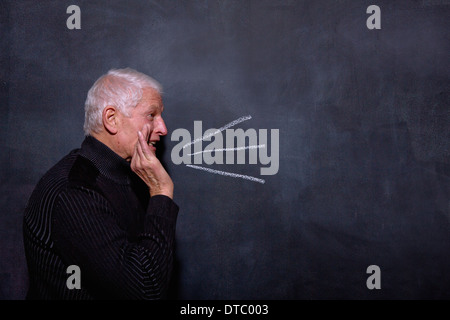 Portrait of senior man in front of blackboard - Stock Photo