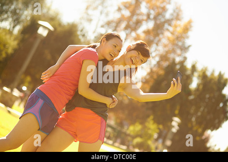 Two young women taking self portrait in park - Stock Photo