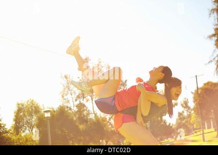 Two young women having fun in park - Stock Photo