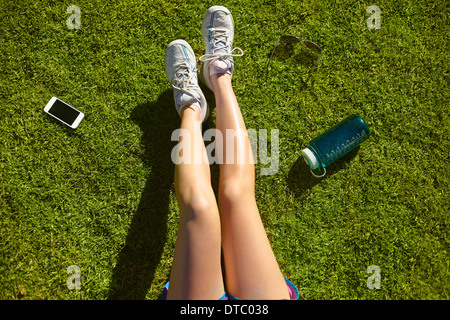 Young woman's legs on sunlit grass in park - Stock Photo