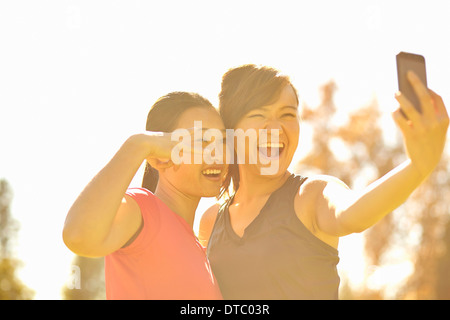Two young women making self portrait in park - Stock Photo