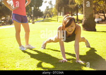 Two young women doing exercises in park - Stock Photo