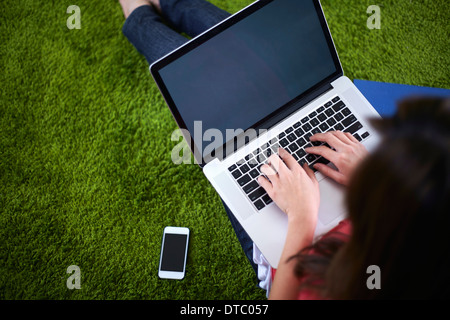 Young woman sitting on rug using laptop - Stock Photo