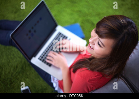 Young woman sitting on rug typing on laptop - Stock Photo