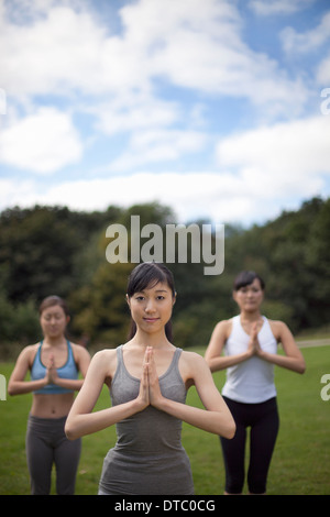 Three young women in park practicing yoga - Stock Photo
