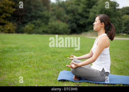 Young woman in park practicing yoga lotus position - Stock Photo