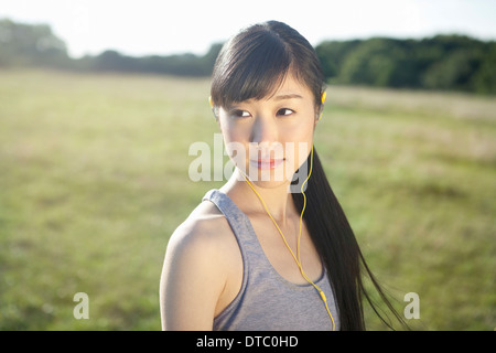 Portrait of young female runner wearing earphones - Stock Photo