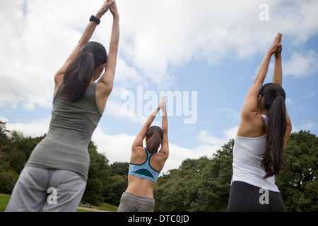 Three young women practicing yoga in park - Stock Photo