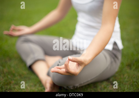 Cropped image of young woman in park practicing lotus position - Stock Photo