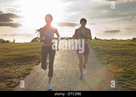 Two young women running on dirt track - Stock Photo