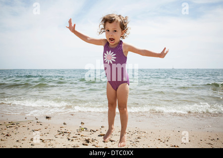 Portrait of jumping female toddler on beach at Falmouth, Massachusetts, USA - Stock Photo