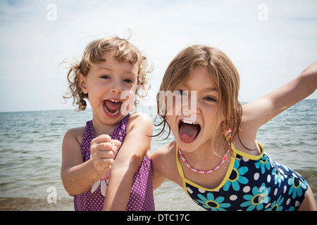 Portrait of two sisters pulling faces on beach at Falmouth, Massachusetts, USA - Stock Photo