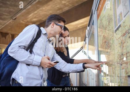 Couple looking at subway map, Los Angeles, California, USA - Stock Photo