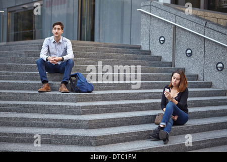 Unhappy couple sitting apart on steps - Stock Photo