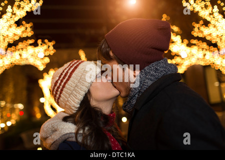 Young couple kissing on street at christmas - Stock Photo