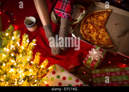 Young woman's legs amongst christmas gifts and pizza box - Stock Photo