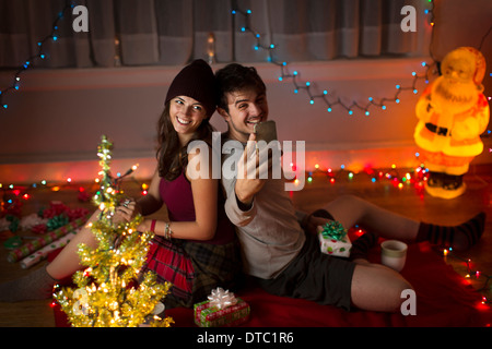 Young couple taking selfie in sitting room at christmas - Stock Photo