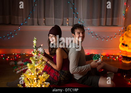 Young couple exchanging gifts in sitting room at christmas - Stock Photo