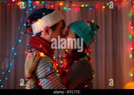 Romantic young couple wrapped in decorative lights at christmas - Stock Photo